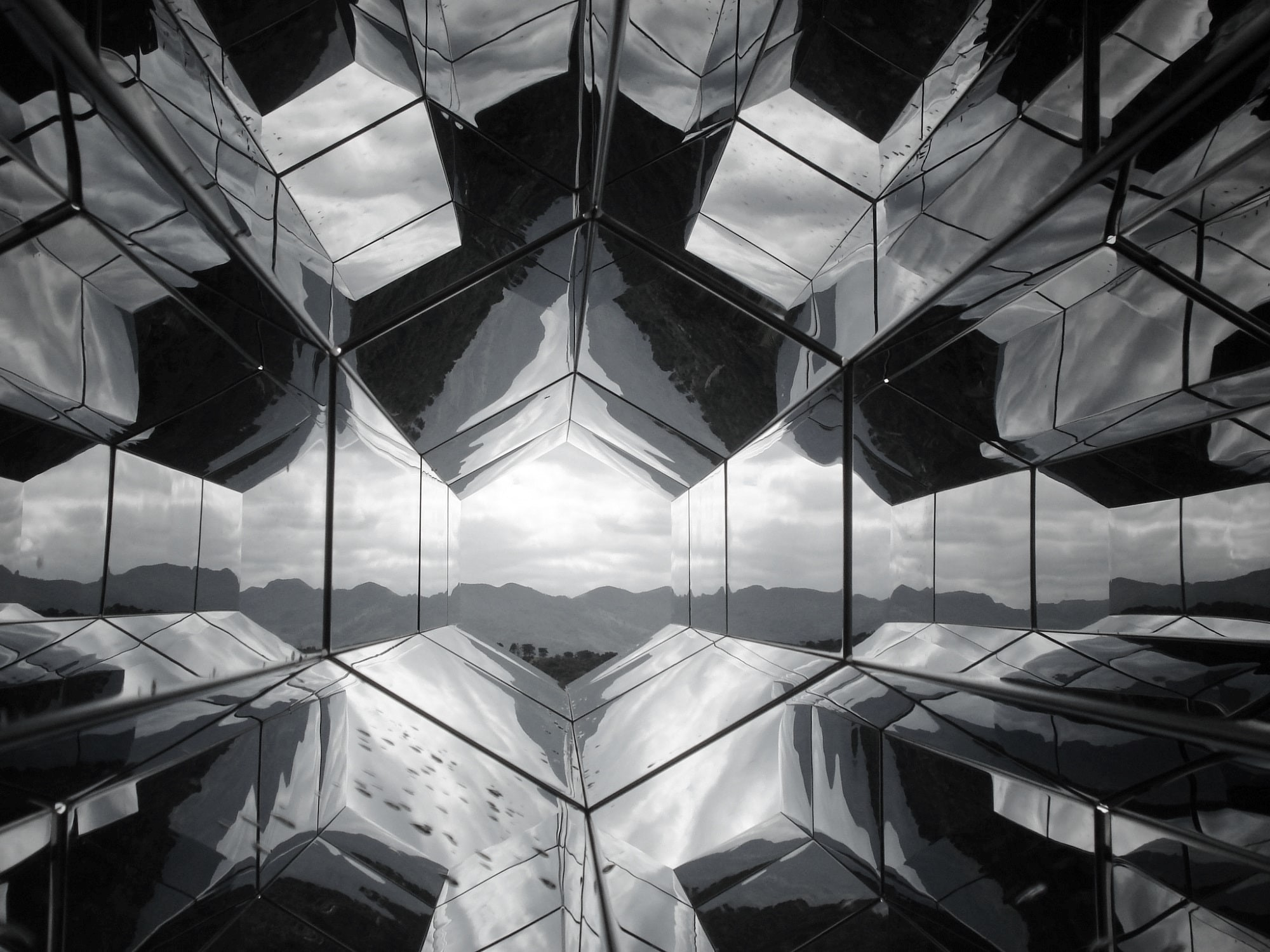 Mirrored surfaces reflect on each other to show mountain view